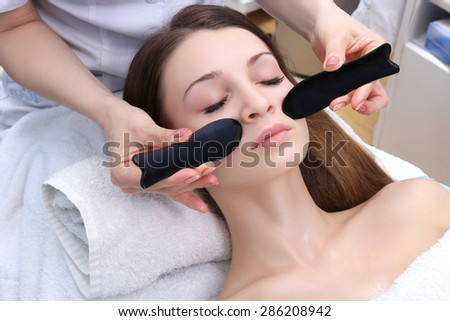 Beauty woman having cosmetic massage, facial treatment, close up.
