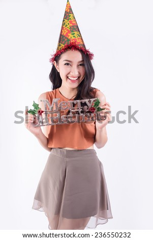 Beauty woman holding Christmas sign and wearing paper hat. Christmas woman portrait of a cute, beautiful smiling mixed Asian model. Isolated on white background.  - stock photo