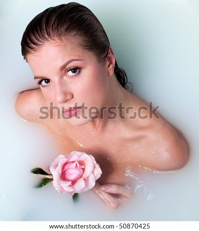Beauty woman in bath with rose in milk water - stock photo
