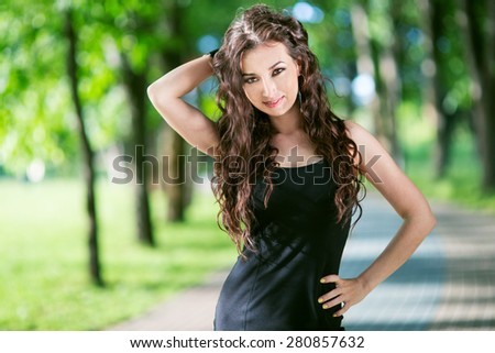 Beauty Woman in Black Dress Outdoor in Green Park - stock photo