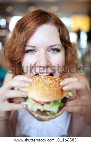 beauty woman in cafe eating hamburger - stock photo