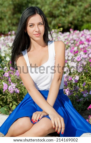 Beauty woman in nature. happy beautiful young woman  smiling sitting near the flower bed