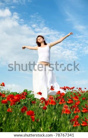beauty woman in poppy field in white dress - stock photo