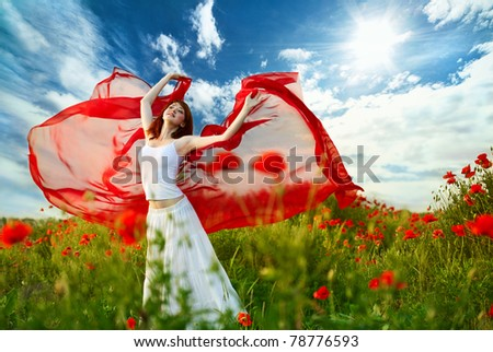 beauty woman in poppy field with red tissue under sky - stock photo