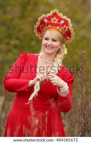 Beauty woman in traditional russian clothes and kokoshnik with long braid outdoor
