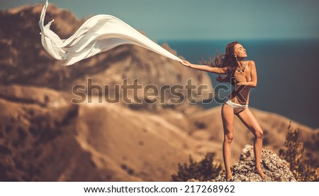 beauty woman on the rock holding  white tissue - stock photo