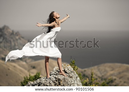 beauty woman on the rock in white tissue - stock photo