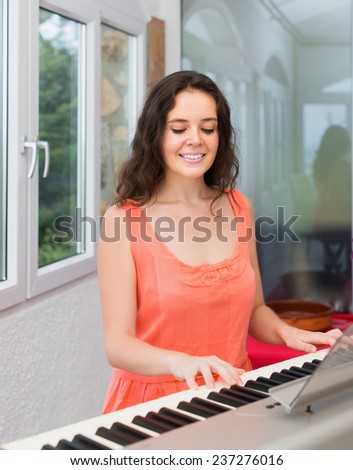 Beauty woman playing piano at home and smiling - stock photo