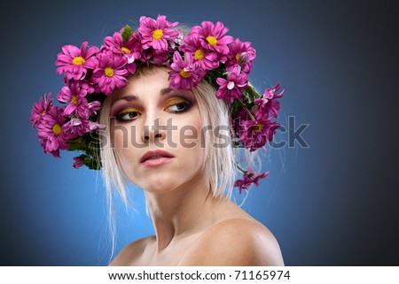 beauty woman portrait with wreath from flowers on head blue background