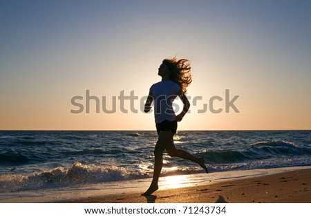 beauty woman run on sea beach on sunset - stock photo