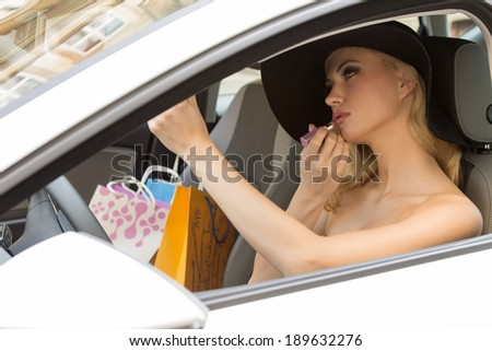 beauty woman sitting in car , with hat and shopping bags near, in act to make up her lips. - stock photo