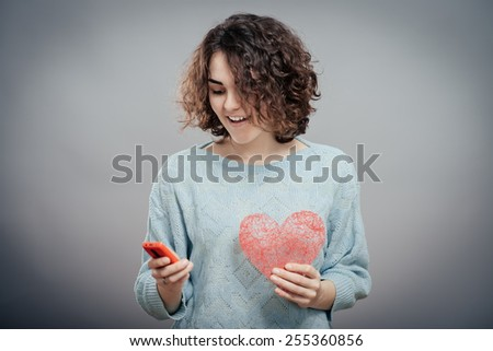 Beauty woman using and reading a smart phone holding red heart isolated