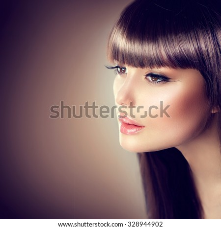 Beauty Woman with beautiful make up and healthy smooth brown hair, fringe hairstyle. Attractive Fashion Model with Long and Healthy Brown Hair. Beauty Brunette Girl on dark background - stock photo