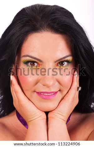 Beauty woman with creative make up holding her face in hands and smile
