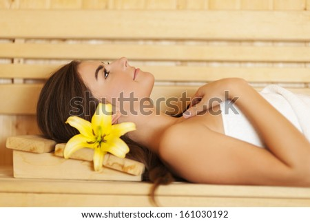 Beauty woman with lily in hair relaxing in sauna  - stock photo