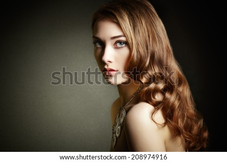 Beauty woman with long curly hair. Beautiful girl with elegant hairstyle. Fashion photo