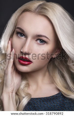 Beauty Woman with Perfect Makeup. Beautiful Professional Holiday Make-up. Red Lips and Nails. Beauty Girl's Face isolated on Black background. Glamorous Woman. Blonde woman with perfect curly hair - stock photo