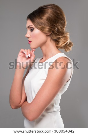 beauty woman with retro hairstyle looking to the side wearing white dress