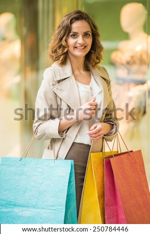Beauty woman with shopping bags in shopping mall is looking at the camera. Sales. Shopping Center.