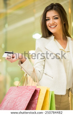 Beauty woman with shopping bags in shopping mall with credit card is looking at the camera. Sales. Shopping Center. - stock photo