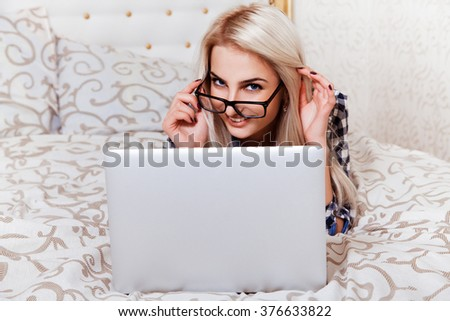 Beauty young blonde woman with blue eyes and laptop smiling on camera in bed. Technology Mobility Education Concept - stock photo