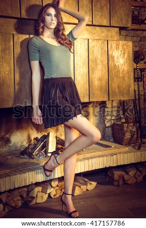 Beauty young brunette woman posing near fireplace at lounge mountain bar. Winter warm evening in interior. Toned image. - stock photo