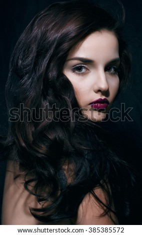 beauty young brunette woman with curly flying hair, femme fatal on black background, low key - stock photo