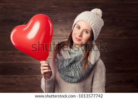 Beauty. Young fashion female model with Valentine Heart  in hand. Love. Beautiful young woman pointing hand, advertising gesture. Valentines Day gift. Wooden background