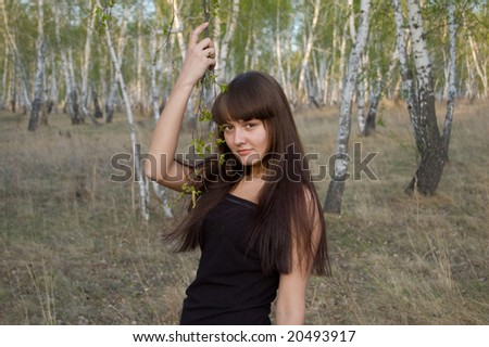 beauty young girl stands with birch twigs - stock photo