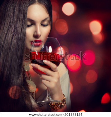 Beauty Young sexy woman drinking red wine over holiday blinking background. Beautiful girl takes glass of red wine over night background. Fashion glamour lady portrait. Wine tasting - stock photo