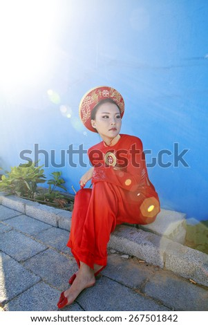 beauty young vietnamese woman in red national ethnic costume, real cheerful girl - stock photo