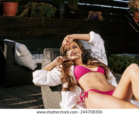 beauty young woman after spa in bikini and robe at hotel resort, on terrace enjoying sun summer - stock photo
