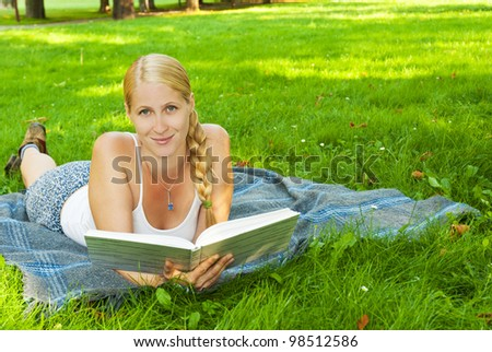 beauty young woman reading book in park