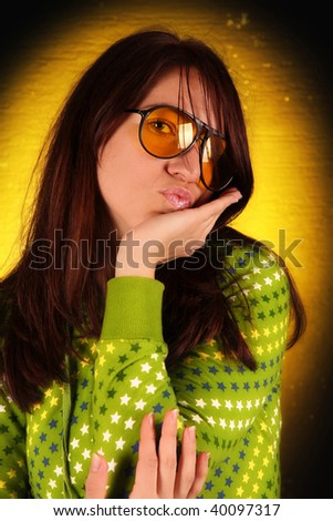 Beauty young woman sending kiss on dark background