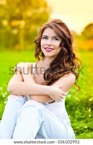 Beauty young woman sitting on the grass and smiling