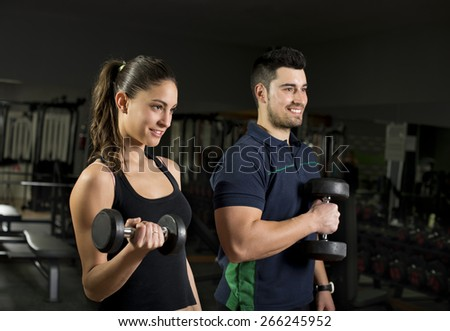 Beauty young woman training lifting weights at gym. Coach is blurred in second frame. - stock photo