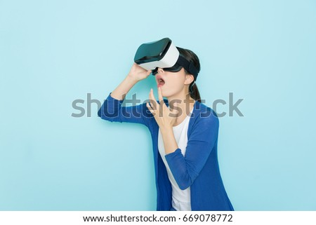 beauty young woman using innovative 3d headset virtual reality technology glasses looking online shopping website getting surprised when she wearing freedom clothing standing in blue background.