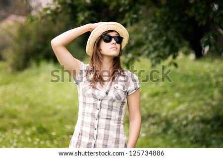 Beauty young woman wearing fedora hat and sunglasses - stock photo