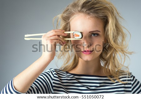 beauty young woman with  rolls Japanese food on gray background