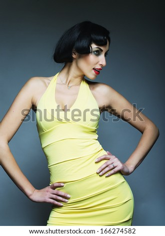 Beautyful woman in vintage style. Black hair and yellow dress. - stock photo