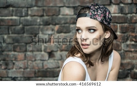beautyful woman with blue eyes wearing hat and white sporty top looking to the side  - stock photo