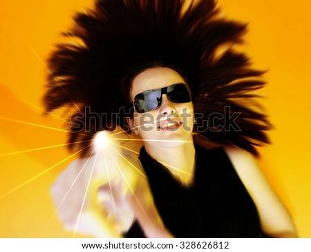 Beautyful woman with sunglasses isolated on orange background. - stock photo