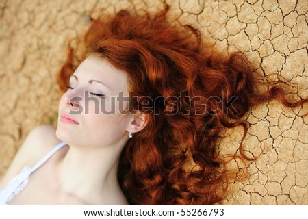 Beauutiful young woman with red hair on the dried up ground