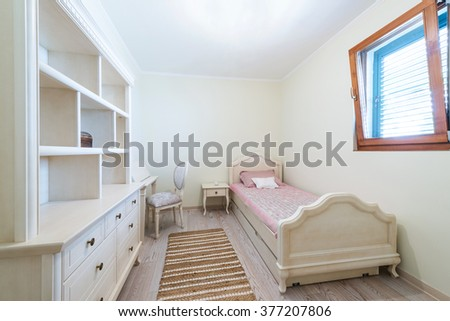 Bed and commode in children bedroom interior - stock photo