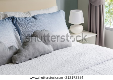 bed and pillows with white lamp on table - stock photo