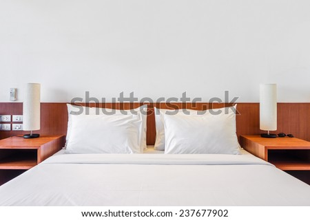 Bed, pillows and lamp in the hotel room - stock photo