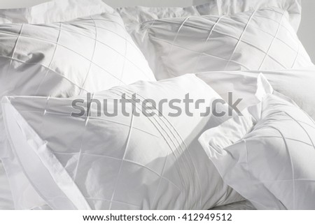bed pillows closeup , classy white covers , in sunny white bedroom  - stock photo