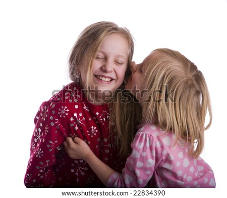 Bed time secret between two sisters - stock photo