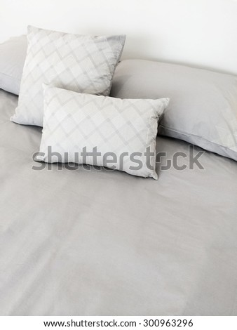 Bed with grey bed linen and pillows.