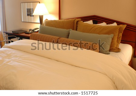 Bed with pillows and comforter in a hotel room - stock photo